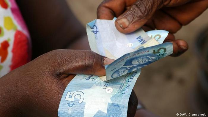 Hands holding Ghana's currency, cedi