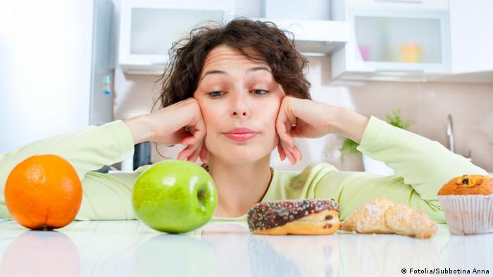 Woman looking at an orange, apple, and pastries