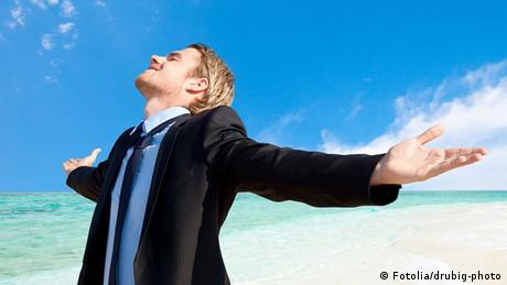 Mann mit Anzug freut sich am Meeresstrand