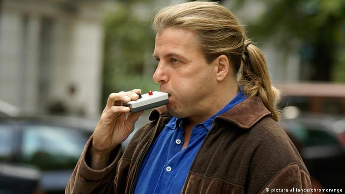 Мужчина контролирует количество алкоголя в крови с помощью алкотестера