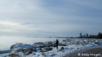 A man braves the cold and walks along the shore of Lake Michigan as temperatures remain in the negative digits