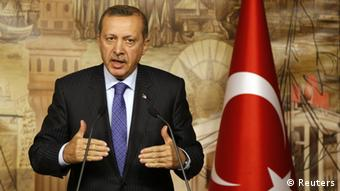 Erdogan, flanked by the Turkish flag, speaks at a press conference
