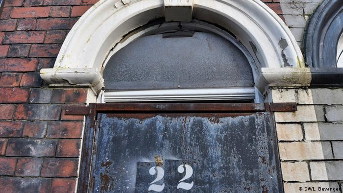 A brick building with a shuttered front door and the address 22 on it.