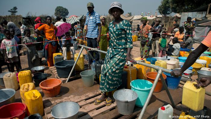 A woman oversees the orderly filling of buckets at a water point in a makeshift camp at Mpoko Airport in Bangui. Photo: AP Photo/Rebecca Blackwell