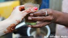 Bansi, a chai wallah near the Bombay High Court in Mumbai, Maharashtra hands a cup of chai to a tourist whose hands are decorated with mehndi.