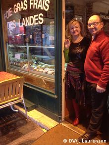 A man and woman smile outside their restaurant during an evening picture.