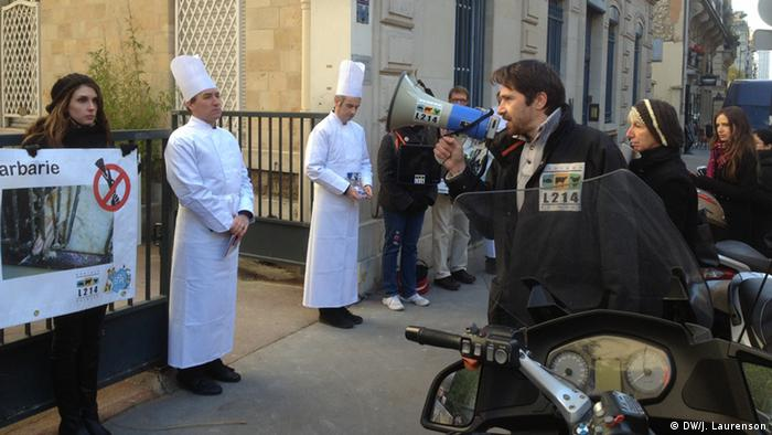 Protestors mingle with two men dressed as chefs.