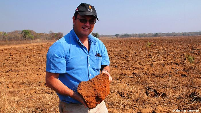 George Allison holding a clump of earth