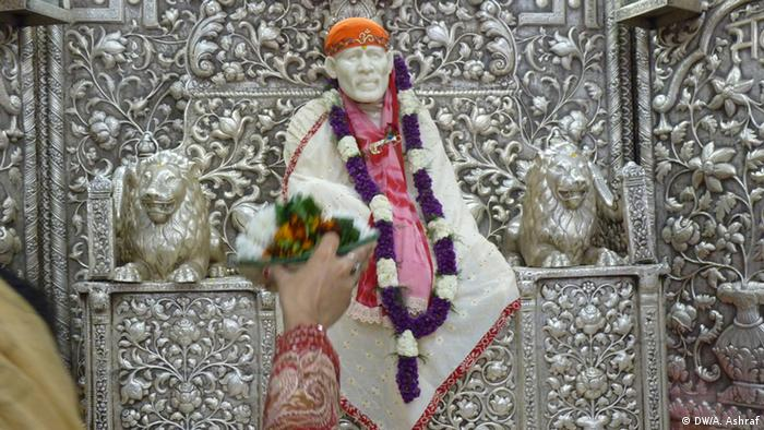 A hand holding up flowers to a god in a New Delhi temple