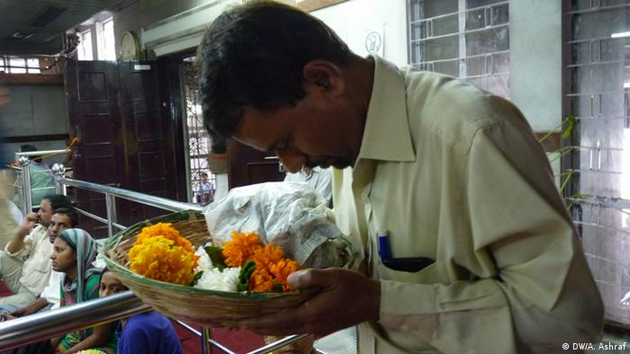 A man holding a basket of flowers bows at a temple in New Delhi (Photo: Anwar Ashraf)