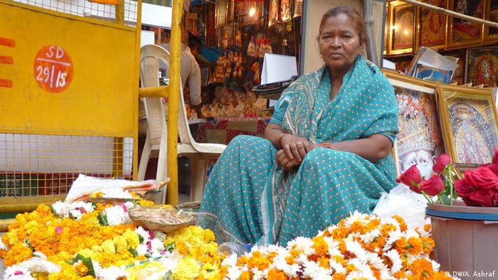 A woman in a blue sari sits selling yellow flowers on a footpath in New Delhi (Photo: Anwar Ashraf)