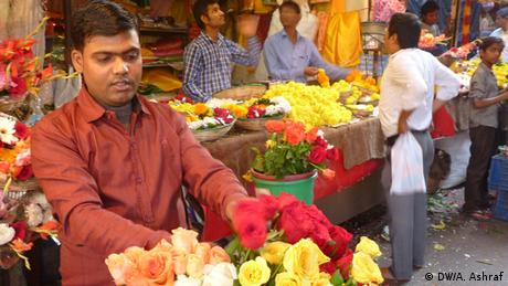 A man sells bright flowers outside a temple in New Delhi (Photo: Anwar Ashraf)