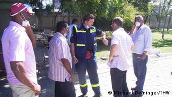 A man gives instructions to four other men wearing purple, short-sleeved shirts.