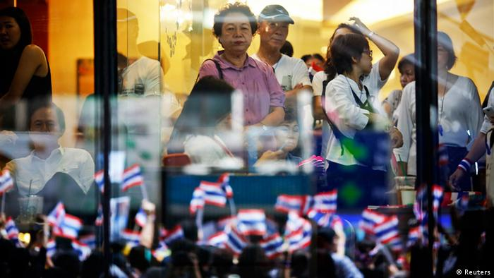 People look on from inside a shopping mall as thousands protest against the amnesty bill in Bangkok's central business district in this November 6, 2013 file photo. For while Thailand, Southeast Asia's second-largest economy, has proven surprisingly resilient to past unrest, analysts see signs of deeper damage this time that could pose longer-term problems for a country already grappling with slowing growth and outflows of global capital from its fragile financial markets. Tourism is taking a hit, infrastructure spending is delayed and investors and consumers are uneasy over a political crisis that promises more violence but no real solution. (Photo: REUTERS/Damir Sagolj/Files)