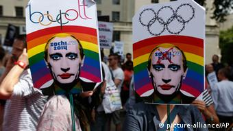 People are holding signs with rainbows and Putin on them (Foto: Lefteris Pitarakis/AP)