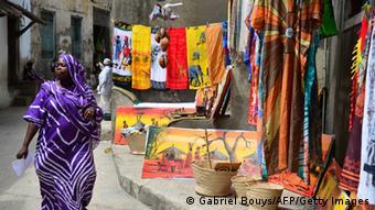 Eine Frau geht an einem Geschäft mit Bildern und Kleidung vorbei (Foto: GABRIEL BOUYS/AFP/Getty Images)