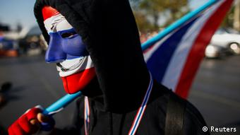An anti-government protester wearing a Guy Fawkes mask painted in the Thai national color, joins others blocking the road at one of major intersections in central of Bangkok January 13, 2014.(Photo: Reuters)