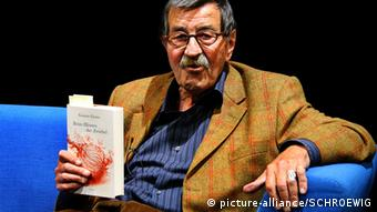 Günter Grass holding a copy of his autobiography Peeling the Onion, Copyright: picture-alliance/SCHROEWIG