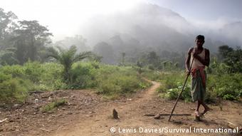 A male member of the Dongria Kondh community in India stands in a forest