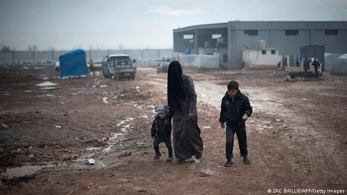 A Syrian women with her children in a refugee camp
