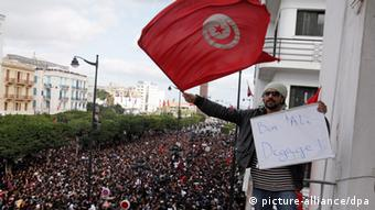 A man waving the Tunisian flag stands in front of protesters (Photo: Lucas Dolega/EPA)