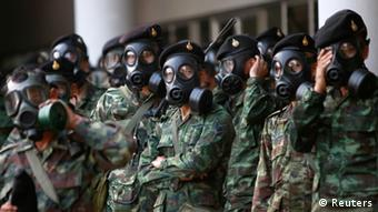 Soldiers wear gas masks as they stand guard at the Thai-Japan youth stadium in central Bangkok December 26, 2013. Thai police fired teargas at anti-government protesters in the capital Bangkok on Thursday after demonstrators tried to disrupt planning for a February election, the first such incident in nearly two weeks.