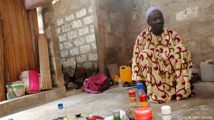 Bildergalerie Voodoo in Westafrika - Voodoo-Priester hockt vor leeren Flaschen, Zigarettenschalen und Süßigkeiten (Foto: Katrin Gänsler)