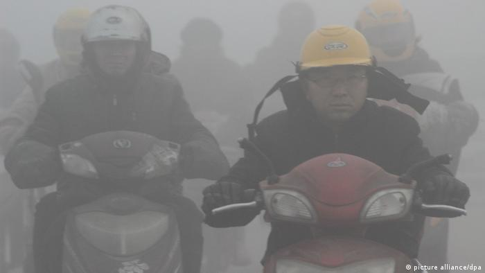 Motorbikers driving through smog in China