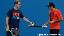 Switzerland's Roger Federer and coach and former Grand Slam champion Stefan Edberg during a practice session at the Australian Open tennis championship in Melbourne, Australia, Wednesday, Jan. 15, 2014. (AP Photo/Mark Baker)