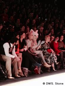 A woman in a cat costume is sitting in the front row at the Lena Hoschek fashion show at Berlin Fashion Week, January 2014, Photo: DW / S. Stone