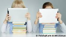 Two young people reading tablets, Copyright: Fotolia/Karin & Uwe Annas