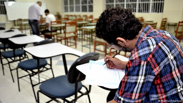 A man in a checkered long-sleeved shirt writes on a worksheet in a classroom setting. Photo: Marina Estarque