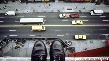 Gestelltes Symbolbild: Blick von oben auf die Schuhe eines vermeintlichen Selbstmörders, der auf dem Fenstersims eines mehrstöckigen Hauses in einer amerikanischen Großstadt steht. Unten fließt der Verkehr auf einer mehrspurigen Straße. (Aufnahme von 1993).