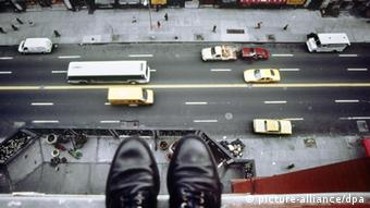 Looking down upon shoes of person standing on ledge high above a street