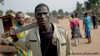 A man with alight brown jacket walks trhough a street with a machete (Foto: Rebecca Blackwell/AP Photo)