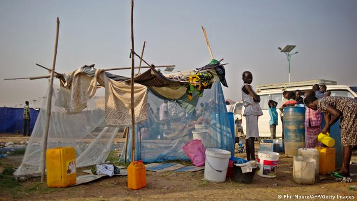 South Sudanese refugees standing outside a tent made of a mosquito net