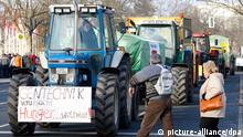 Ausstellungsbesucher gehen am Samstag (22.01.2011) vor der Messe Berlin an einer Traktorenkolonne vorbei, an deren erstem Traktor ein Schild mit der Aufschrift Gentechnik verursacht Hunger... weltweit! befestigt ist. Vor dem Messegelände, auf dem zur Zeit die Grüne Woche stattfindet, haben sich Bauern mit rund 70 Traktoren eingefunden, um dem Staatssekretär vom Bundeslandwirtschaftsministerium eine Protestnote zu überreichen. Foto: Florian Schuh dpa