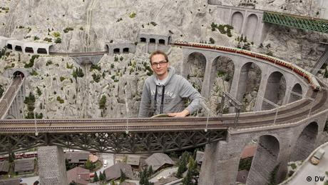 Sebastian, Bandmitglied von EINSHOCH6, sitzt in der Modelleisenbahn-Landschaft in Hamburg. (DW)
