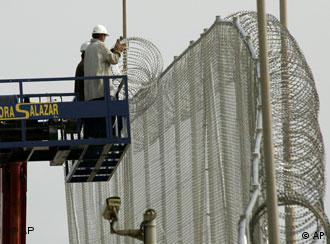 Workers fix razor-wire to a fence in the Spanish enclave of Melilla, Spain Monday Oct. 10, 2005. The Spanish authorities have begun work on raising the hight of the fences from three metres to six metres after hundreds of immigrants managed to climb over and enter Melilla. (AP Photo/Alvaro Barrientos)