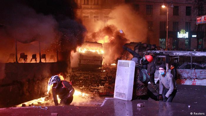 Протестующие в Киеве на фоне горящих автомобилей