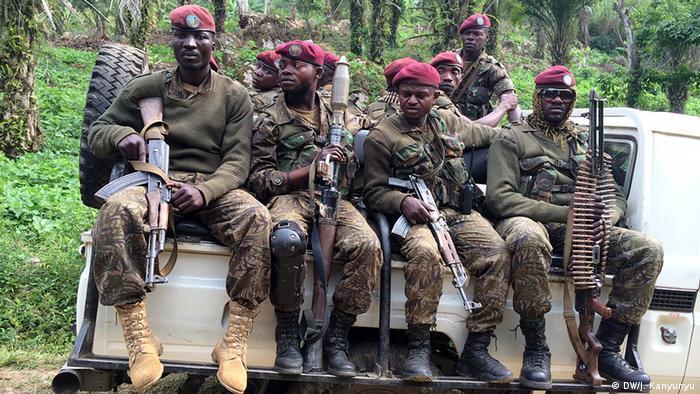 Bewaffnete kongolesische Soldaten sitzen auf der Ladefläche eines offenen Kleintransporters
