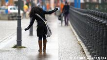 Eine junge Frau versucht sich am 20.01.2014 auf dem durch Blitzeis glatten Fußweg am Ufer der Spree in Berlin auf den Beinen zu halten. Foto: Soeren Stache/dpa +++(c) dpa - Bildfunk+++