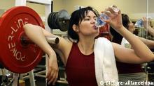 Fitness Frau im Fitness-Studio trinkt Wasser