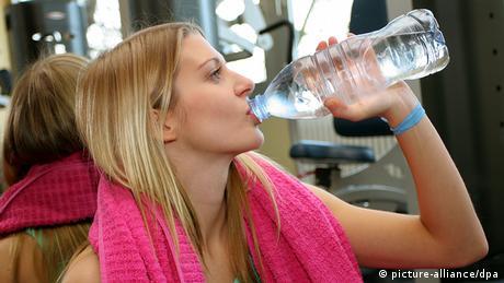 Deutschland Fitness Frau im Fitness-Studio trinkt Wasser