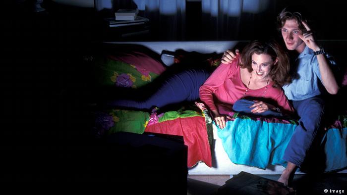 Una pareja viendo la tele a oscuras.