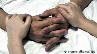 Young hands grip the wrists of an older person lying in a bed