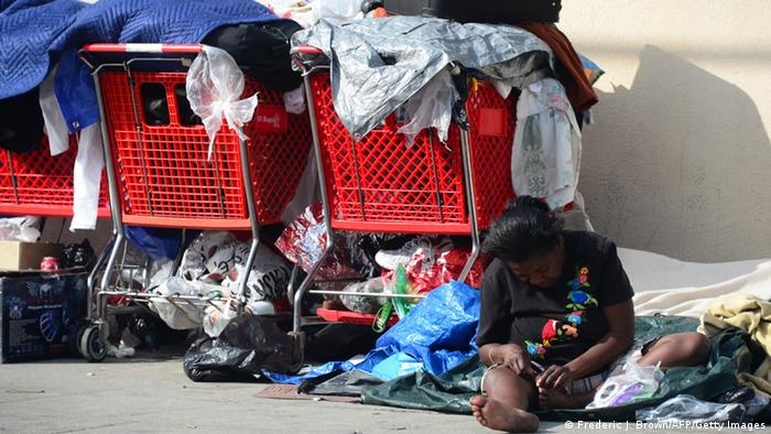 A homeless woman in Los Angeles sits among her belongings in three large shopping carts.
