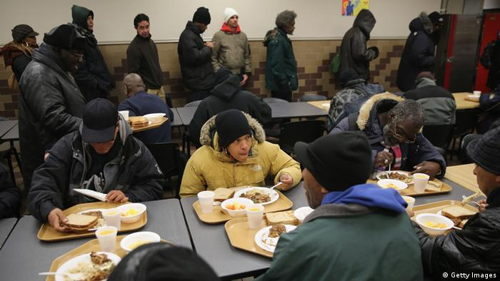 People eat dinner at a soup kitchen run by the Food Bank For New York City. (Photo: John Moore/Getty Images)