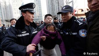 Liu Chunxia, a supporter of Xu Zhiyong, one of China's most prominent rights advocates, is detained by policemen while she gathers with other supporters nearby a court where Xu's trial is being held in Beijing January 22, 2014 (Photo: REUTERS/Kim Kyung-Hoon)