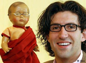 Doll maker Marcel Offermann with a previous creation, the Dalai Lama